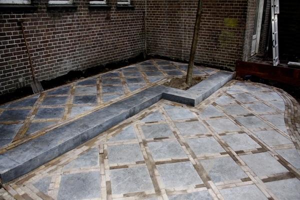 Sierbestrating van nieuw gebakken walen met stoepje van Portugese tegels in Haarlem