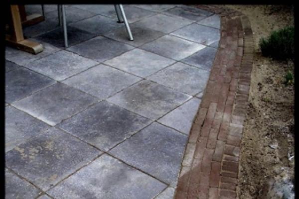 Detail van terras van natuurstenen tegels met rand van gebakken walen in Overveen