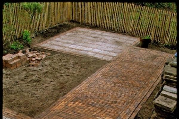 Bestrating van natuurstenen tegels met rand van gebakken walen in Amstelveen