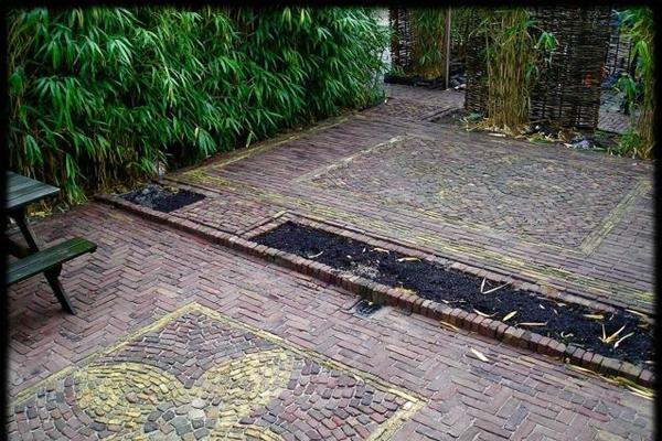 Sierbestrating van oude walen met antieke tegels en muurtjes van betonnen muurelementen in Haarlem_0287